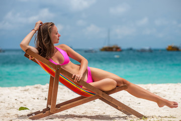 Woman in lounger on tropical beach