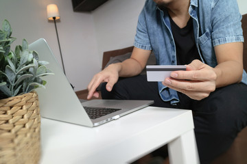 hipster hand using laptop compter,holding cradit card payments online shopping or business,sitting on sofa in living room,green apples in wooden tray