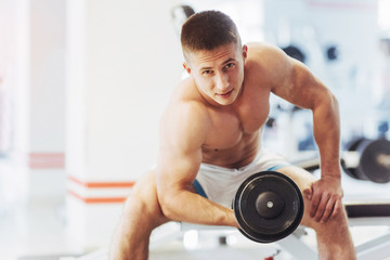 Beautiful athletic bodybuilder guy, carries out exercises with d