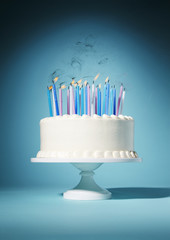 Birthday cake with lit candles against blue background