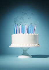 Candles blown out on birthday cake against blue background