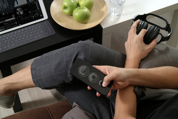 hipster hand using smart phone for mobile payments online business,headphone,sitting on sofa in living room,green apples in wooden tray,graphic interfce icons virtual screen