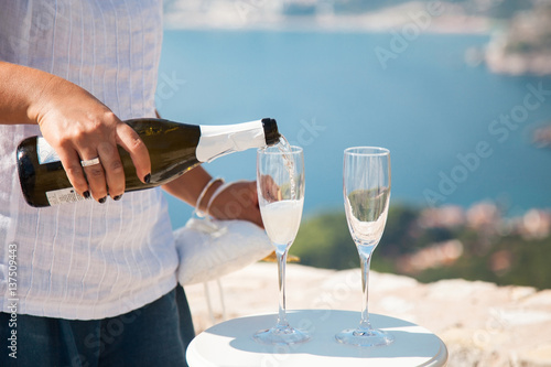 Groom As Waiter Pours Champagne Into Wineglasses From Bottle For