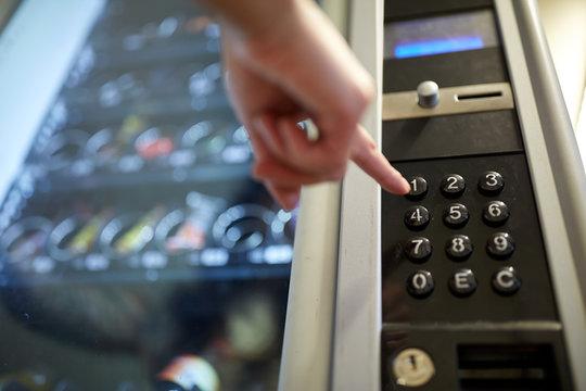 hand pushing button on vending machine keyboard
