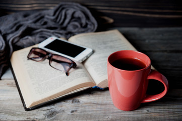 grey cozy knitted scarf with cup of coffee or tea, phone, glasses and open book on a wooden table.