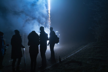 people standing and watching fireworks, silvester, dark, silhouette