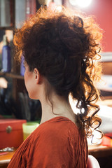 woman with raised long curly hair at hairdresser