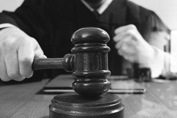 justice and law concept.Male judge in a courtroom with the gavel,working with smart phone,digital tablet computer docking keyboard,eyeglasses,on wood table,black and white