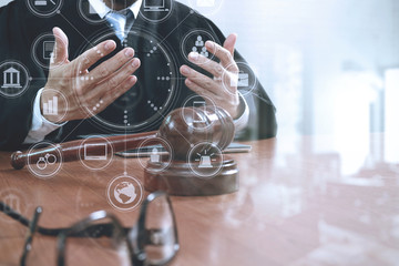 justice and law concept.Male judge in a courtroom with the gavel,working with smart phone,digital tablet computer docking keyboard,eyeglasses,on wood table,virtual interface graphic icons diagram