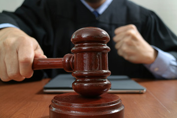 justice and law concept.Male judge in a courtroom with the gavel,working with smart phone,digital tablet computer docking keyboard,eyeglasses,on wood table,filter