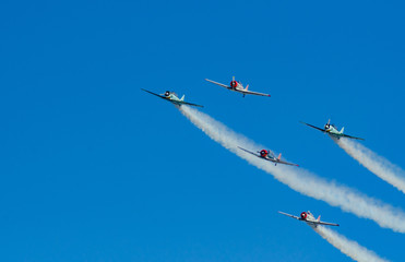 Vintage planes in formation with smoke trails