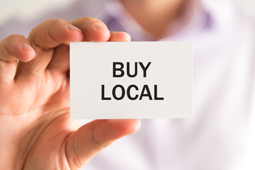 Businessman holding a card with text BUY LOCAL