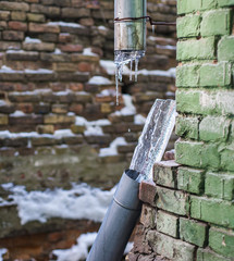 Broken frozen downspout with ice inside