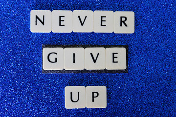 Never Give Up Letters On Blue Glitter Background