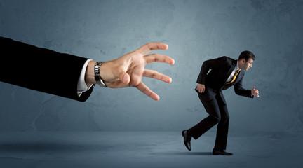 Business man running away from a huge hand concept