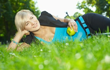 Businesswoman lying grass with apple in hand