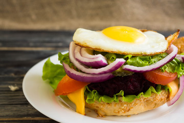 Hamburger with fried eggs and beetroot on a wooden table and ingredients
