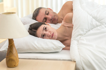 The depressed woman lay near man on the bed