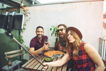 Friends at table posing for phone on selfie stick