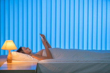 The young woman lay on the bed and phone. Evening night time