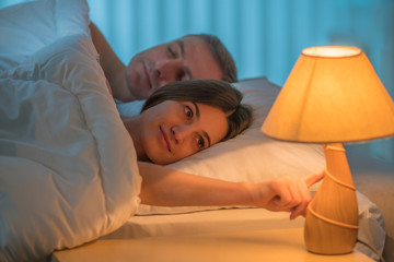 The woman lay on the bed with man. Evening night time