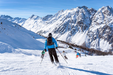 Skiers skiing downhill in high mountains and sunny day