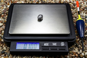 Lead weight for fishing float with pocket scale on the stony ground