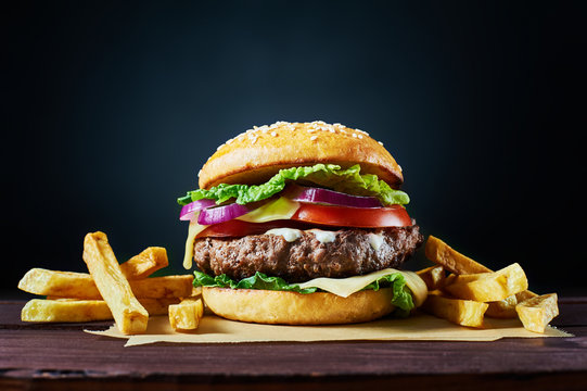 Craft beef burger and french fries on wooden table isolated on dark background.