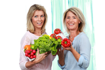 Two mature girlfriends with fresh vegetables