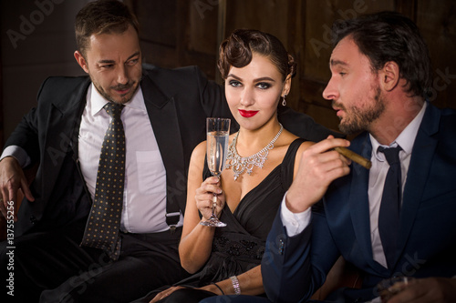 d89d641213 Rivalry or competition between two handsome rich executive men for elegant lady  with red lips. Pretty lady sitting with glass of champagne.