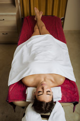 Woman lying back on a massage table with closed eyes and relaxes. Getting Spa Treatment in Spa Salon, top view