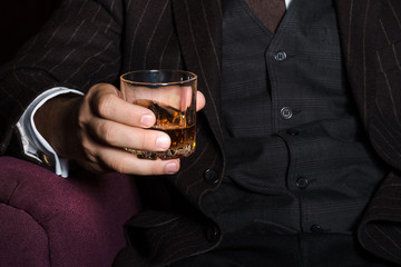 Closeup of serious businessman holding whiskey illustrate executive privilege concept