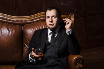 Handsome man is smoking cigar and drinking whiskey