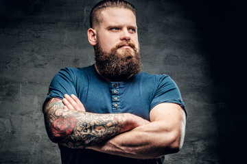 Bearded fat male with tattoo on arms.