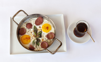 Fried eggs with sausage in pan