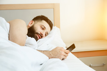 Bearded man lying in morning bed with phone using app or reading news feed