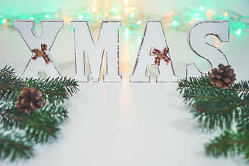 Of Christmas composition of wooden letters XMAS, lights and fir branches with cones with room for your text. Bright background for the basic design