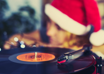 Blurred Image of Christmas. Gramophone playing a record. Blurred a girl in a Christmas cap with red hair listening to a vinyl record in the background