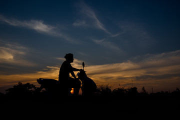 Silhouette of a man sitting on a motorcycle. Sunset