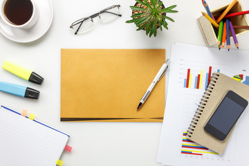 Top view accessories business office desk.mobile phone,coffee,notepaper,pen,letter,colorful charted,pencil,eyeglasses on white office desk with copy space.