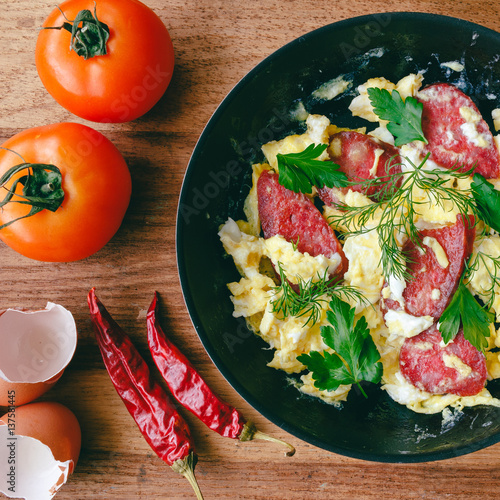 Fresh cooked scrambled eggs in pan with sausage and herbs. Tomato ...