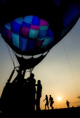 Silhouette of people with hot air balloon with beautiful colored envelope at sunset, backlit by sunlight photography