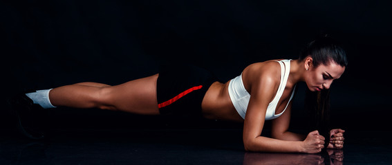 Athletic young woman doing planking exercise against black background. Sporty woman in sportswear with perfect fitness body.