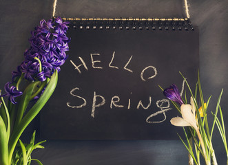 Spring composition with flowers and chalk board