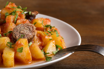 Potatoes stew with pork sausage and herbs on plate