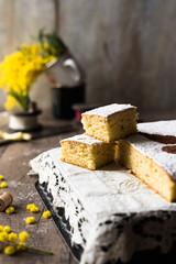 torta gialla con zafferano tipica della tradizione di Firenze e fiori di mimosa sfuocati sullo sfondo