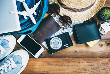 Overhead view of Hipster Traveler accessories and items on brown wooden background ,Travel and Holiday concept.
