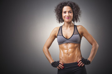 Image of a beautiful fitness woman posing on grey background