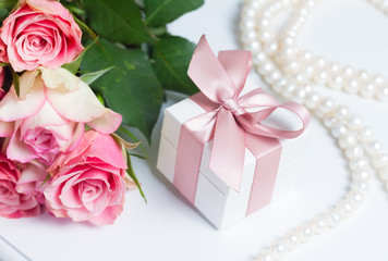 Gift box with pink ribbon and rose flowers on white table