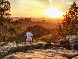 Nature photographer takes photos on peak of rock.